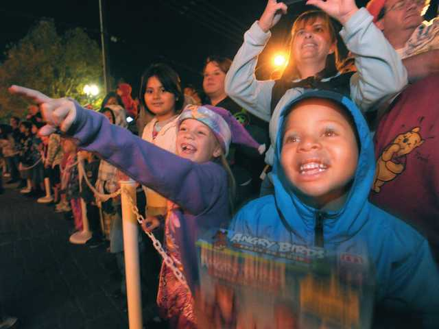 Jenna Root, 7, left, and Christopher Apolinario, 6, point to the Holiday Toy Express.