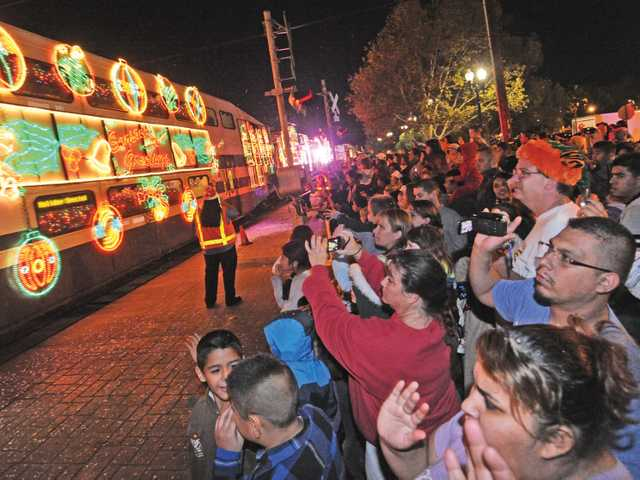 Hundreds watch as the Holiday Toy Express pulls into the Jan Heidt Metrolink station.