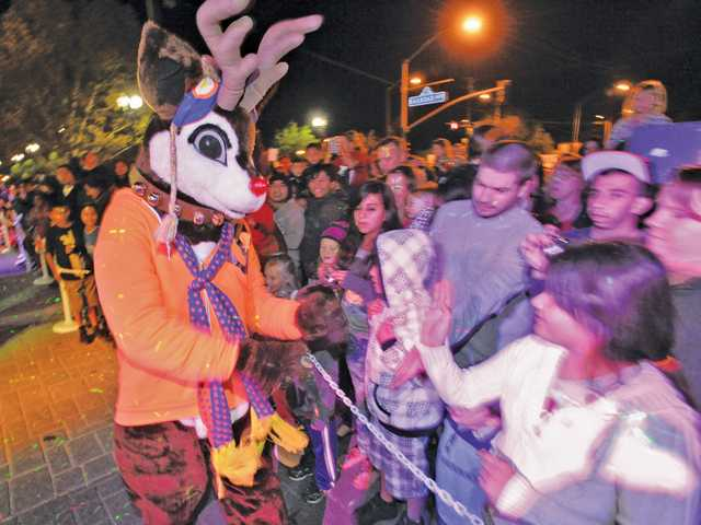 Rudolph the Reindeer shakes hands with some of the hundreds gathered to watch the show of the Holiday Toy Express after it pulled into the Jan Heidt Metrolink Station in Newhall on Sunday.