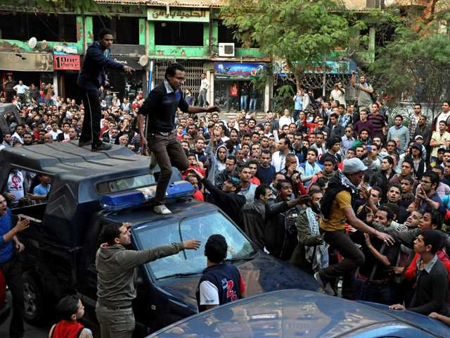 Egyptians stand on police vehicles during the funeral of Gaber Salah, who was who was killed in clashes with security forces in Cairo.