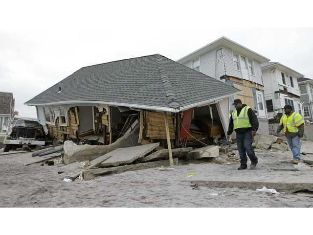 Utility workers walk past a badly damaged house in the Belle Harbor neighborhood of the Rockaways, in New York.