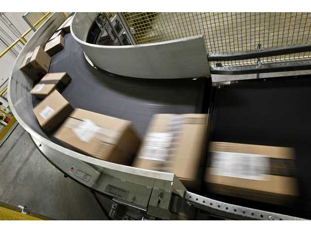 Packages ready to ship move along a conveyor belt at the Amazon.com 1.2 million square foot fulfillment center on Monday, in Phoenix. Americans clicked away on their computers and smartphones on Cyber Monday, which is expected to be the biggest online shopping day in history.