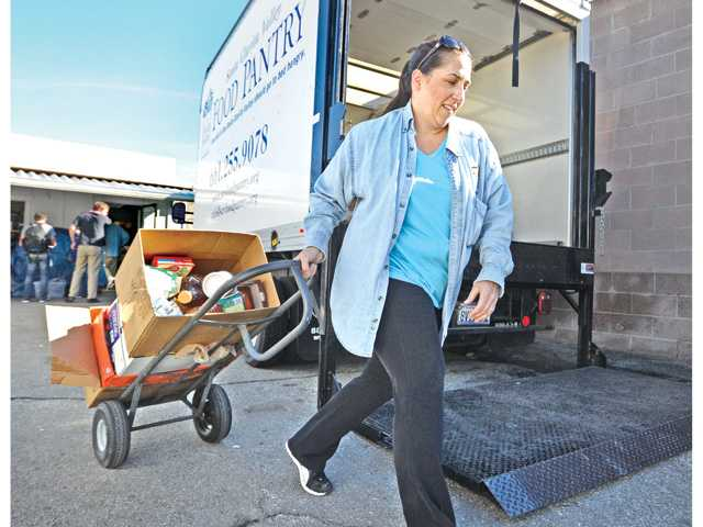 Senior Outreach Coordinator Lily Wolfe wheels a cart of donated food to a truck to be moved to off-site storage for future use at the SCV Food Pantry in Newhall on Wednesday.
