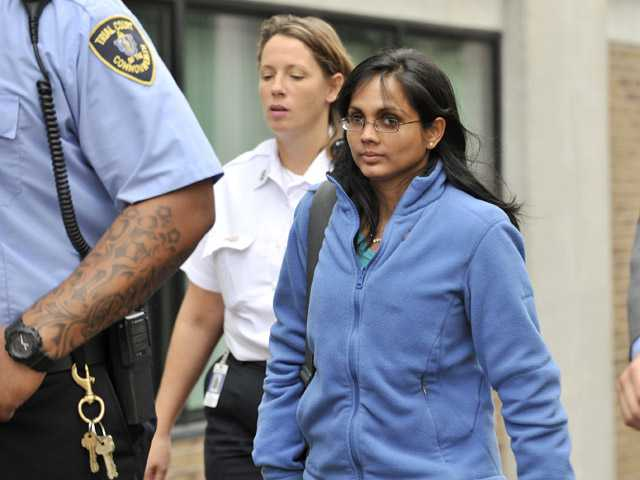 In an Oct. 10, 2012 file photo, Annie Dookhan, center, leaves a Boston courthouse escorted by court officers and her lawyer.