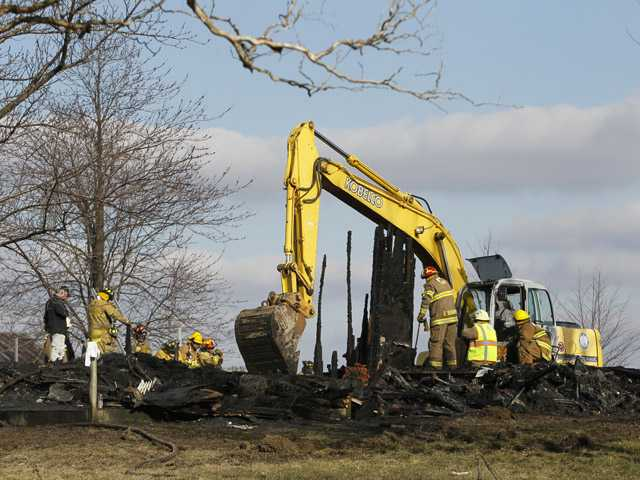 Fire officials use a front end loader to sift through the rubble after a fatal fire in Reed Township in rural Seneca County, Ohio.