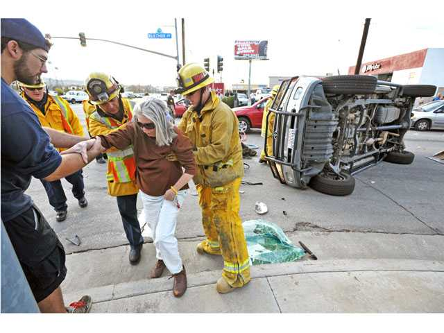 Firefighters assist a passenger after she is rescued from a Toyota Tundra that overturned in a collision with a Honda Civic at Ruether Avenue and Soledad Canyon Road in Canyon Country on Tuesday afternoon.