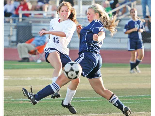 Saugus forward Brenna Savoie, left, takes a shot on goal against a Lancaster defender in the second half on Tuesday at Saugus High School.
