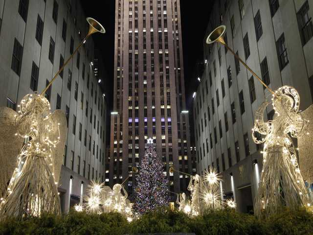 Angels decorations frame the Rockefeller Center Christmas tree after it was lit during the 80th annual tree lighting ceremony at Rockefeller Center in New York, Wednesday.