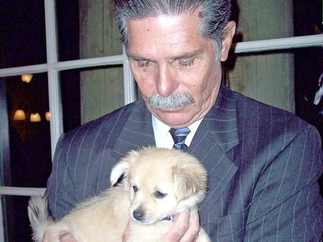 Don Rodriguez holds a rescued puppy that was auctioned to raise funds for the Zonta Club of SCV.