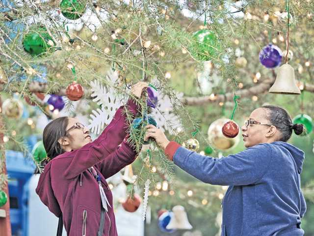 Volunteers Shulin Chung, left, and Shavon Jackson hang some of the 2,000 Christmas ornaments on the tree Wednesday at Henry Mayo Newhall Memorial Hospital.