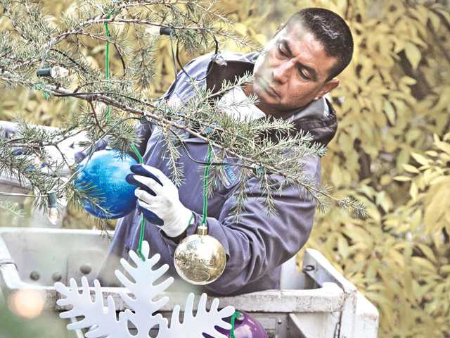 Andy Gump employee Danny Antunes, standing in a cherry picker, hangs Christmas ornaments on a 42-foot tree on Wednesday in Valencia.