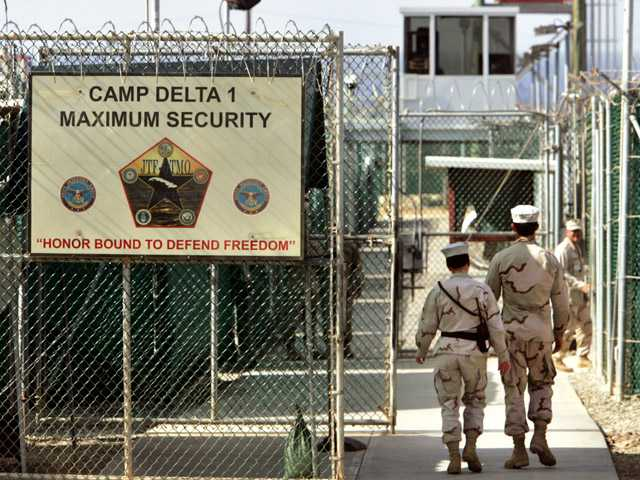 In this June 27, 2006, photo, reviewed by a U.S. Department of Defense official, U.S. military guards walk within Camp Delta military-run prison, at the Guantanamo Bay U.S. Naval Base, Cuba.