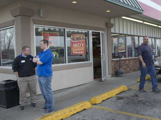 An unidentified customer walks out of the Trex Mart convenience store, right, while manager Chris Nauerz, left, and son of the owner Baron Hartell stand outside, in Dearborn, Mo., Thursday.