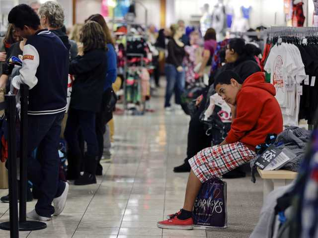 A teenage boy waits for his family to finish shopping at a J.C. Penney store in Las Vegas, on Nov. 23.