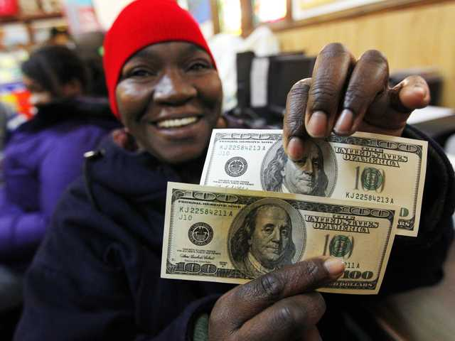 Charlotte Muhammad holds up two $100 dollar bills she got from Secret Santa, at St. Joseph's Social Service Center in Elizabeth, N.J., on Thursday. The wealthy philanthropist from Kansas City, Mo. known as Secret Santa distributed $100 dollar bills to needy people at St. Joseph's and other locations in Elizabeth.
