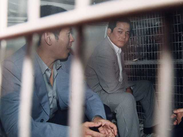 "In this 1999 photo, Macau triad ganster Wan Kuok-koi as ""Broken Tooth Koi"", right, and his brother Wan Kuok-hung are seen on a police van."