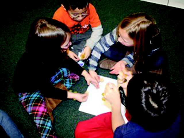 Children playing dreidel at Temple Beth Ami Hanukkah celebrations last year.
