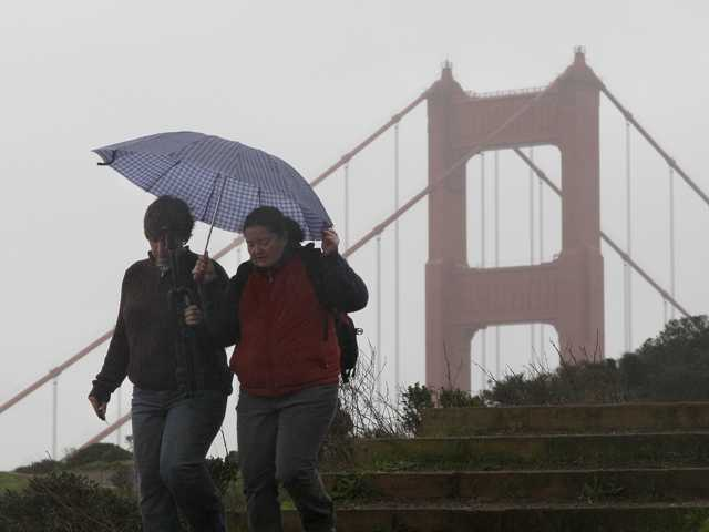 Women walk under an umbrella in front of the Golden Gate Bridge at the Marin Headlands in Marin County, Calif., Thursday, Nov. 29, 2012. The National Weather Service says that by late morning Thursday 1 inch of rain had fallen in several hours across the western side of the county. Much of Northern California is under a variety of warnings and advisories for rain, snow and high winds.