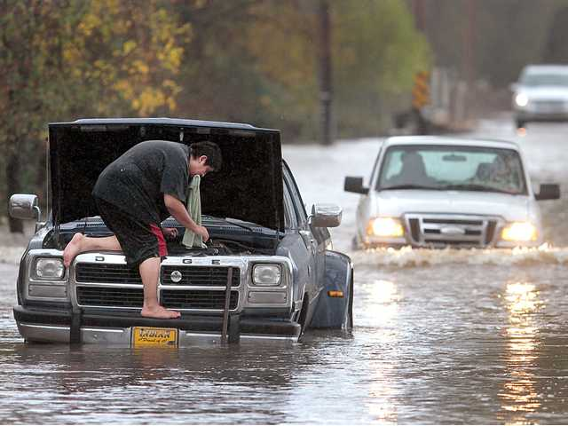 Milton Lopez of Windsor, attempted to drive through flood waters on Mark West Station Road at Starr Road, Friday, in Windsor, Calif.