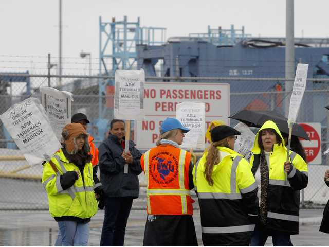 Clerical workers picket in the rain at entrance to Pier 400 at the Port of Los Angeles on Thursday.