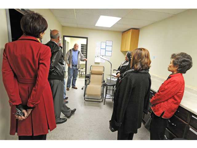 Stan Nagle, center, discusses the new dental clinic to attendees of an open house at the Bridge to Home shelter in Saugus on Friday.