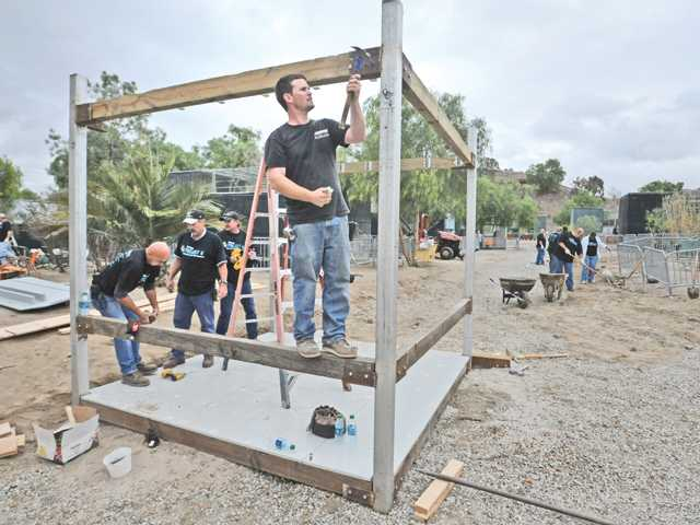 Carpenter Nick Mulhern pounds through a bolt as he works on a visitor's photo booth while joining 150 Six Flag Magic Mountain employees who participated in the annual Project 6: Day of Service by completing upgrades of landscaping, electrical lighting, fencing, painting, and equipment storage at the Gibbon Conservation Center in Saugus on Friday.