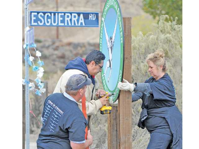 From left, Wes Demrest, Mario Aguilar, and Lima Tinto-Selk hang a sign as they join 150 Six Flag Magic Mountain employees who participated in the annual Project 6: Day of Service.