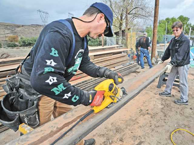Carpenters Rob Ravana, left, and Tim Dofflow cut planks for fencing while joining 150 Six Flag Magic Mountain employees who participated in the annual Project 6.
