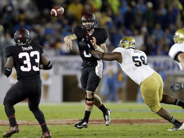 Stanford quarterback Kevin Hogan throws under pressure from UCLA defensive end Datone Jones (56) during the first half of the Pac-12 championship game in Stanford on Friday.