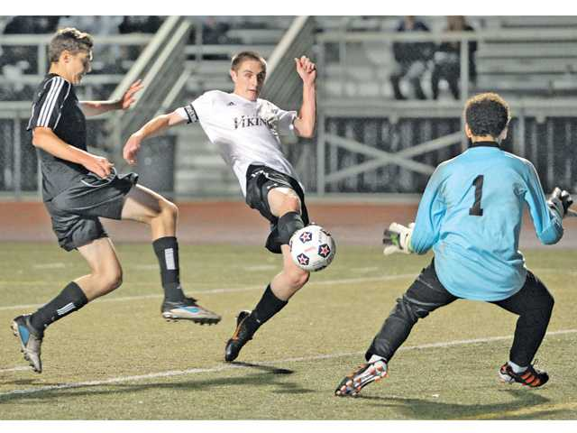 Valencia's Marc Silingardi, center, slips a goal past Stockdale goalkeeper Ben Shenouda (1) on Friday at Valencia High.