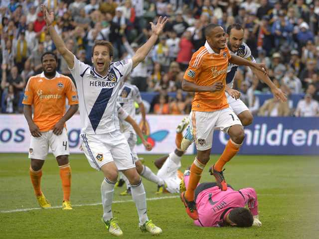 Los Angeles Galaxy forward Mike Magee, second from left, celebrates a goal along with midfielder Landon Donovan, right, by defender Omar Gonzalez as Houston Dynamo defender Jermaine Taylor, left, and midfielder Ricardo Clark, look on and goalkeeper Tally Hall lays on the ground during the second half of their MLS Cup  match Saturday in Carson. The Galaxy won 3-1.