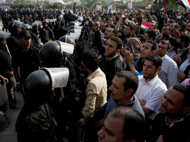Supporters of Egyptian President Mohammed Morsi chant slogans at riot police in Cairo, Egypt.