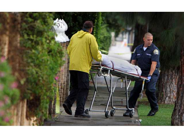 A covered body is removed from the scene after police found the bodies of four people outside a boarding house in Northridge.