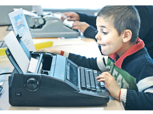 Simeone Spitale, 5, is intrigued by the clacking of the electric typewriter on display.