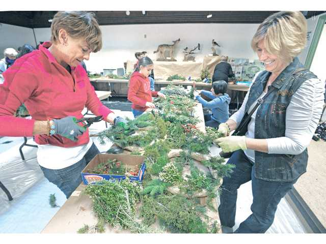 Jana Vannini, left, and Diana Morrissey, of Valencia, create holiday wreaths at the Placerita Nature Center's annual Holiday Craft Fair on Saturday.