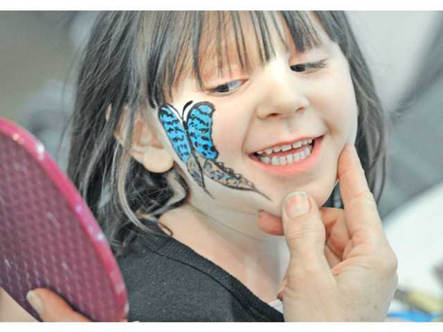 Katherine Roberts, 4, gets a look at the butterfly painted on her face at the Placerita Canyon Nature Center's Holiday Craft Fair on Saturday.