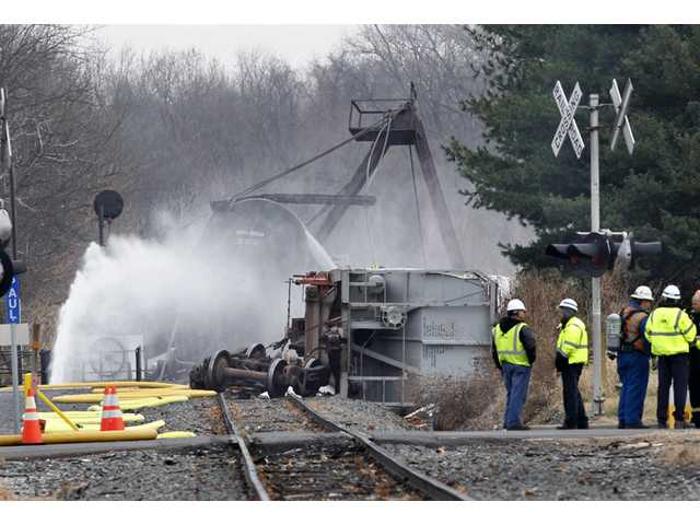 Crews continue to spray water on derailed freight train tank cars in Paulsboro, N.J., Saturday.