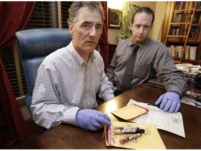 Cook County Sheriff Tom Dart, left, and sheriff's detective Jason Moran with three recently discovered vials of murderer John Wayne Gacy's blood.