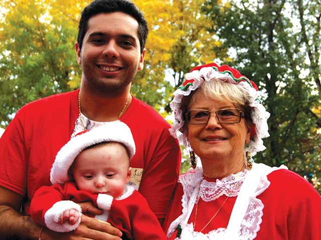 Proud dad Alan Armani and his son, Princeton, born just five months ago, pose with Mrs. Claus at the annual tree-lighting event at Henry Mayo Newhall Memorial Hospital on Sunday.