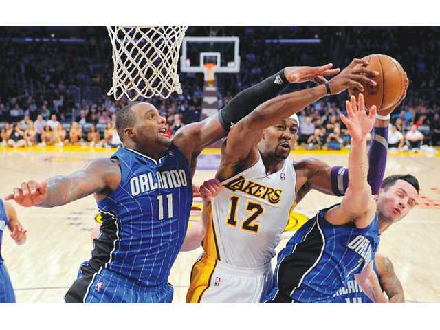 Los Angeles Lakers center Dwight Howard, center, goes up for a shot as Orlando Magic forward Glen Davis, left, and guard J.J. Redick defend on Sunday in Los Angeles.