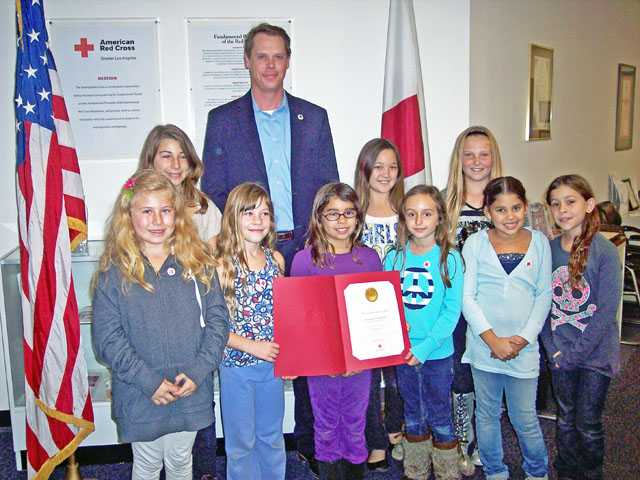 Students from Highlands Elementary School recently raised nearly $1,000 to benefit vicitms of Superstorm Sandy. They presented their donation to Jeff Baumgartner, executive director American Red Cross Antelope Valley Chapter. He presented the girls with a certificate of appreciation. From left, Reese Lewis, Eden Lewis, Claire Stein-Wendt, Amanda Salinas, Katie Thanaet, Sydney Morrell, Brieahna Patterson, Ryann Meilleur and Isabella Perez.