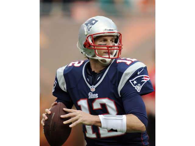 New England Patriots quarterback Tom Brady (12) looks to pass against the Miami Dolphins on Sunday in Miami.