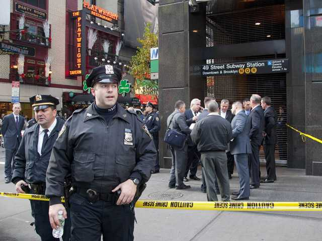 Police officers stand outside a New York subway station after a man was killed after falling into the path of a train, Monday.