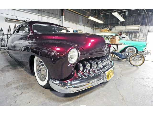 A 1950 Mercury Coupe, left, and a 1957 Buick Estate Wagon at Mike Fennel Restorations in Saugus.