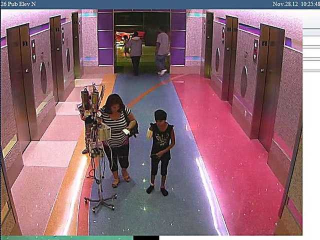 In this hospital surveillance photo released by the Phoenix Police Department on Monday, a woman is seen with her 11-year-old daughter, a leukemia patient who had her arm amputated and a heart catheter inserted due to an infection.