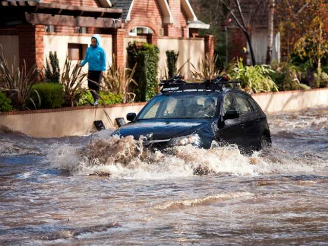 Sherri Twardzik of Sacramento navigates a flooded McKinley Boulevard and 34th Street Dec. 2 in Sacramento, Calif. Residents hunkered down Sunday as a powerful storm drenched the area with pounding rain and strong winds. AP Photo/The Sacramento Bee, Randy Pench