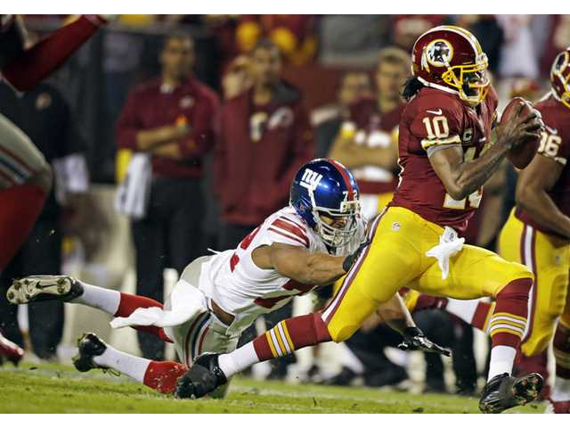 New York Giants defensive end Osi Umenyiora (72) reaches for Washington Redskins quarterback Robert Griffin III (10) in Landover, Md. on Monday.