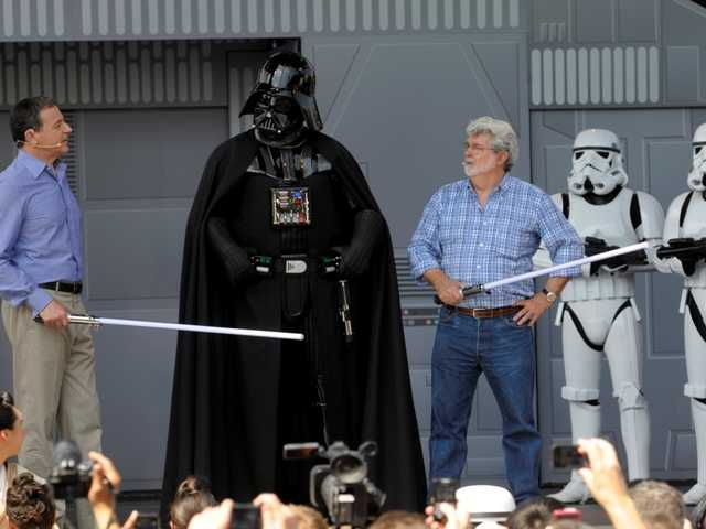 Disney CEO Robert Iger, left, and Star Wars creator George Lucas, third from right, talk to the Star Wars movie character Darth Vader, center, onstage at the Disney Hollywood Studios theme park May 20, 2011.