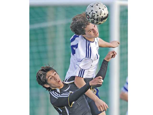 West Ranch's Eduardo Trujillo, right, heads the ball in front of Eastside's Edwin Quiroz on Tuesday at West Ranch High.