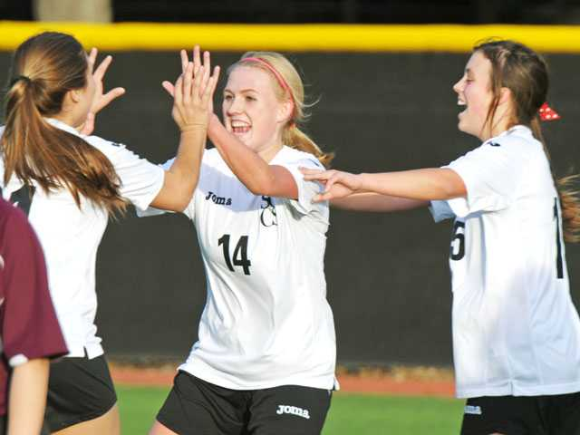 Santa Clarita Christian's Sarah Holzer (14) celebrates her goal with teammates Kim Curry, left, and Gracie Gwinn on Tuesday at Reese Field at The Master's College on Tuesday.